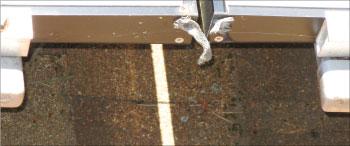 Photo 5. Improper use of module bonding screw and copper in braid touching aluminum.