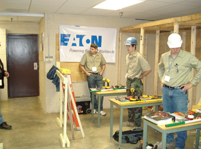 Photo 2. Students Arrive Prepared. Each student that participated in the Residential Wiring or Motor Control portions of the program had a cubicle with a desk where they arranged their tools. Safety was a key aspect and each student was reviewed for clothing which included eye protection, hard hats and proper clothing.