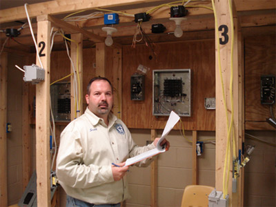 Photo 3. Judges. After the students completed the practical installation portion of testing, volunteer judges reviewed and scored each student's work. Scott Jolliff reviews the Gold Medalist's work.