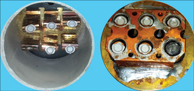Photo 3. This is a photo showing the interior of a 600-amp fuse after the sand filler has been removed.  This fuse opened during an overload condition.   You can see how five of the six alloy contact points melted and released; when the last one interrupted the flow of current, it arced and caused the burned sixth contact.  Please note in the left photo you can see the short-circuit elements which are still intact; these are the webs which melt out during a high fault current condition.