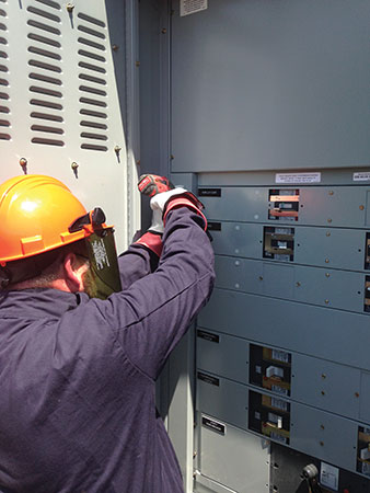 Photo 1. An electrical inspector wearing proper PPE for the incident energy available inspects this electrical equipment. Even inspectors need to dress for success and adhere to the requirements of NFPA 70E.